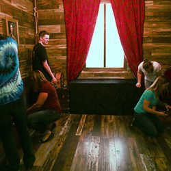 an image of 5 young men and women looking for clues inside the Captain's Quarters escape room